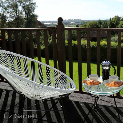 Professional property photography of breakfast scene on balcony overlooking Romney Marsh in Kent by Liz Garnett